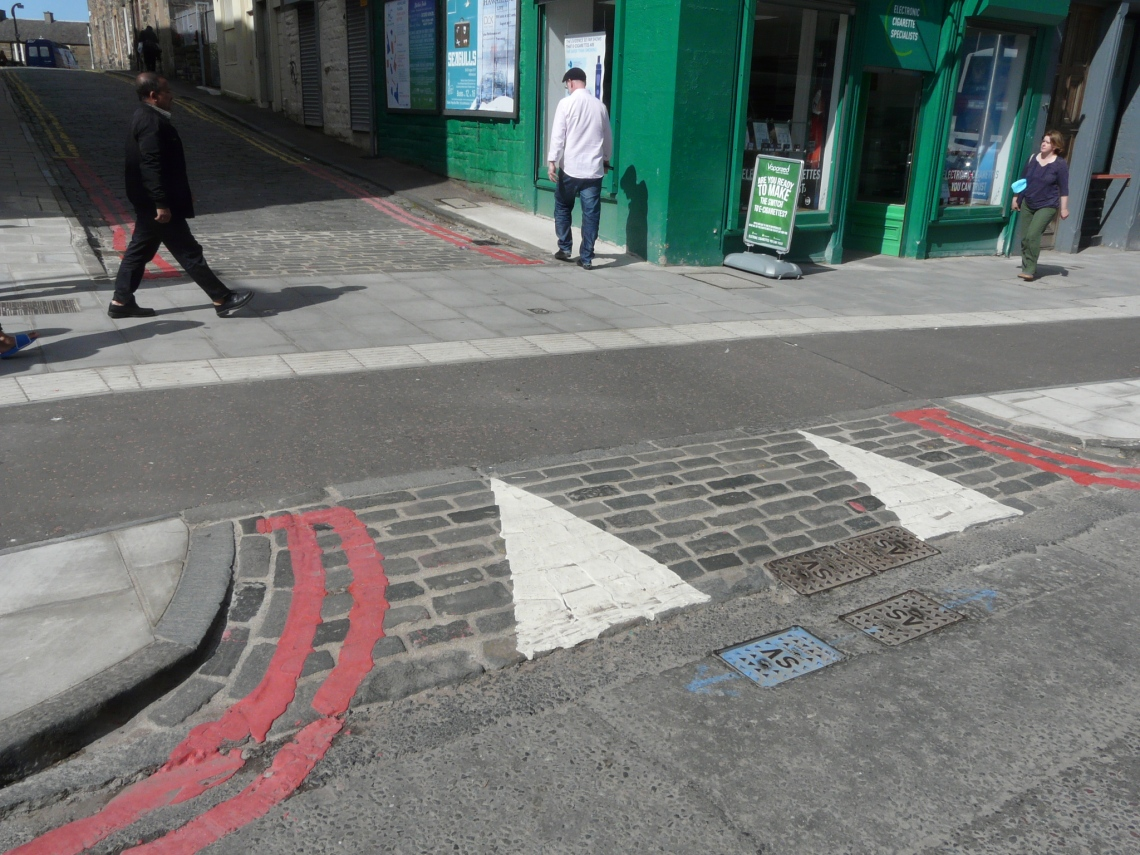 Image shows same continuous footway, but with lines of paints added to part of it to control parking.