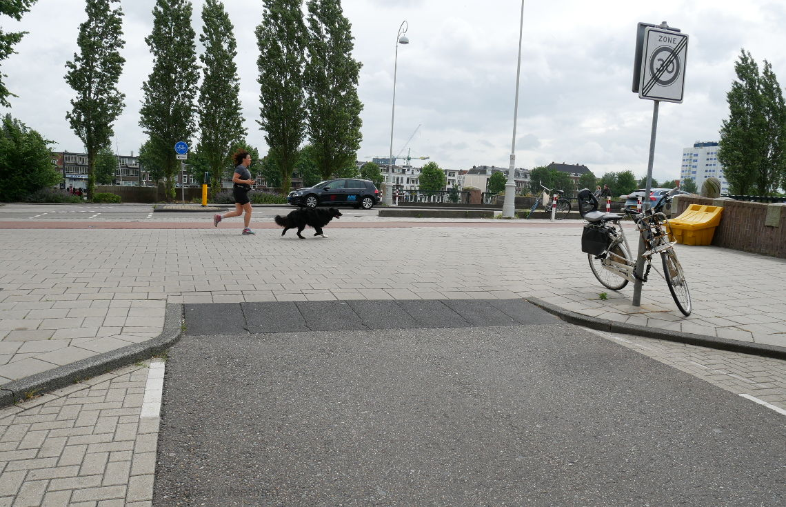 Image shows a woman and dog running along a piece of footway over which people might drive to access a side road.