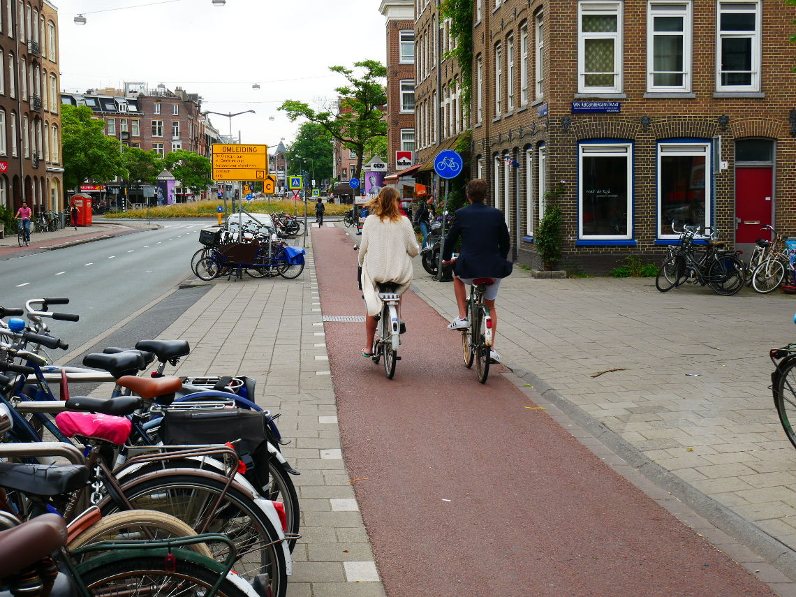 Image shows two people cycling along a cycle track talking to one another, paying little attention to the roads to either side of them, as the track passes across a section of continuous footway.